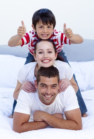 Happy parents and son in bed with thumbs up photo