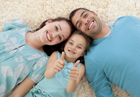 dads: Parents and little girl on floor with thumbs up Stock Photo