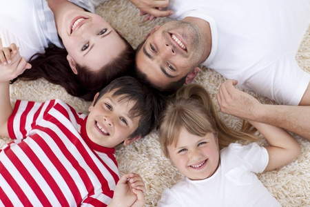lying on floor: High angle of family on floor with heads together