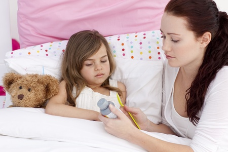 Mother giving her daughter cough medicine photo