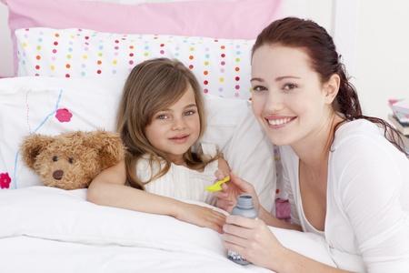 tos: Niña enferma en la cama teniendo tos medicina