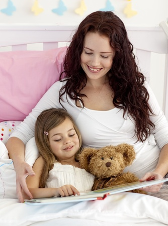 Mother and daughter reading in bed photo