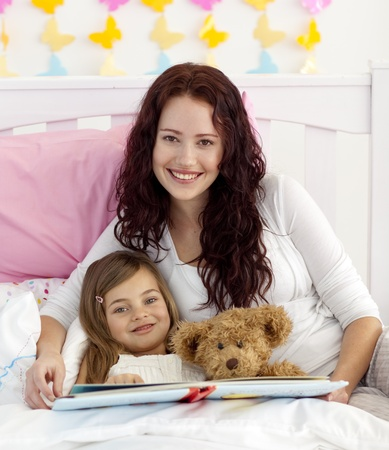 Smiling mother and daughter reading in bed photo
