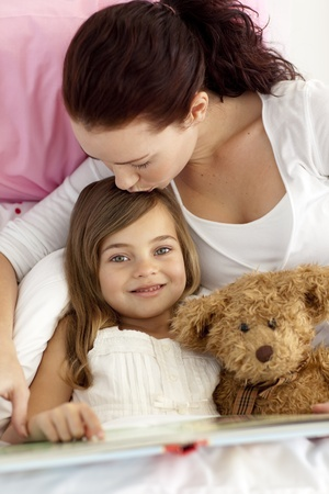 Mother kissing her daughter reading in bed Stock Photo - 10239063