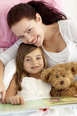 Beautiful mother and daughter reading a book Stock Photo - 10238443