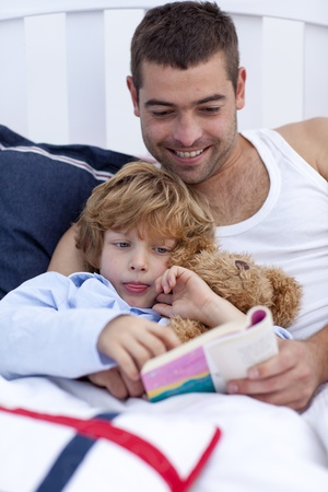 Little boy reading with his father a book  photo