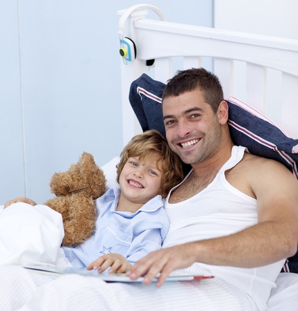 Smiling father and son reading a book in bed photo