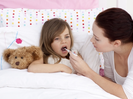 sick day: Mother taking her daughters temperature with a thermometer Stock Photo