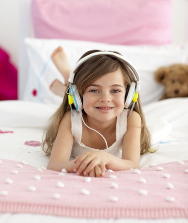 Smiling girl listening to the music in bed photo