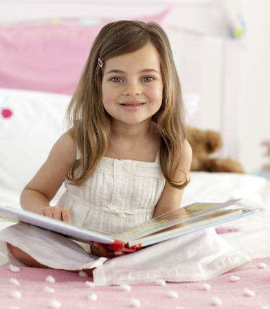 Smiling little girl reading in bed photo