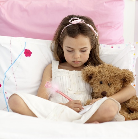 Little girl writing in bed photo