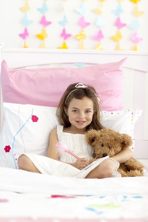 Smiling little girl writing in bed photo