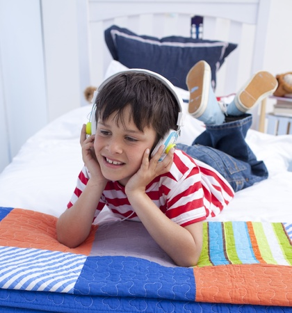 Boy relaxing in bed listening to music photo
