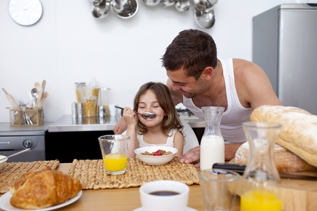 Little girl enjoying her breakfast with her father photo