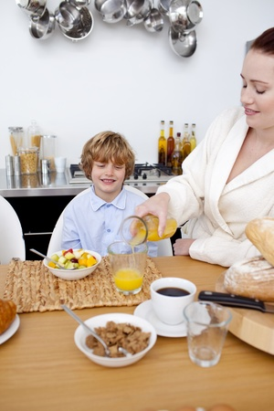 Boy having breakfast with his mother photo