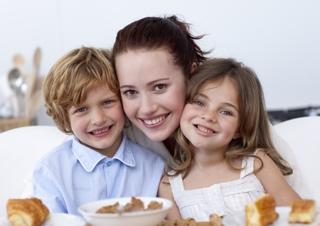 Smiling children having breakfast with their mother photo