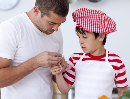 Boy hurt his finger and father treating it photo