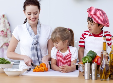 Mother and children cutting vegetables in kitchen photo