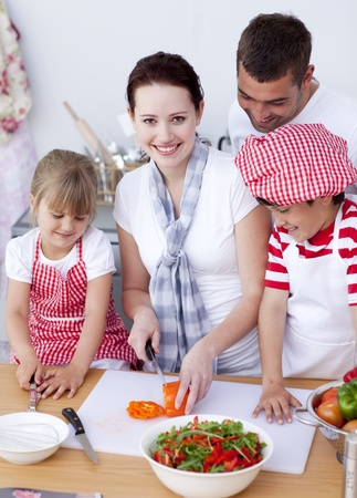 Happy family preparing a salad in kitchen photo