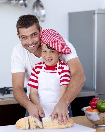 Smiling father and son cutting bread photo