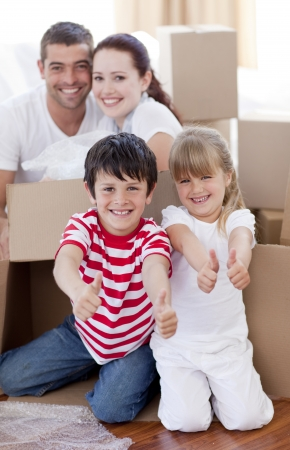 Family moving house with boxes and thumbs up photo