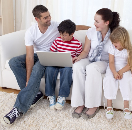 Smiling family in living-room using a laptop photo