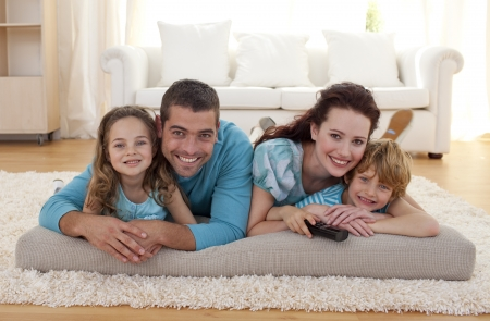 lying on couch: Smiling family on floor in living-room Stock Photo
