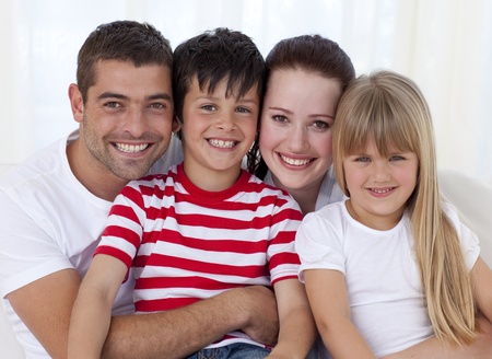 Portrait of smiling family sitting on sofa together photo