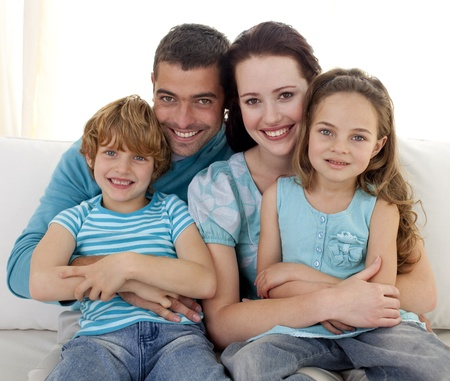 family sofa: Family sitting on sofa together