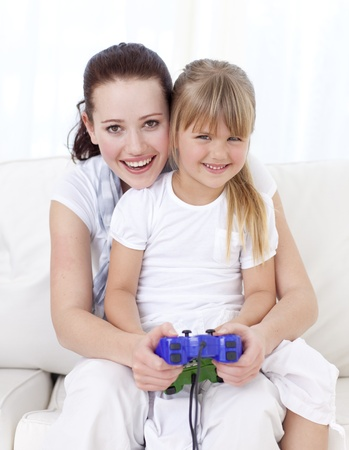 Mother and daughter playing video games at home photo