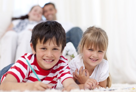 Smiling brother and sister painting on floor in living-room Stock Photo - 10244188
