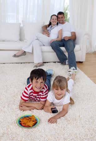 pareja en casa: Ni�os felices viendo la televisi�n en piso en Sal�n