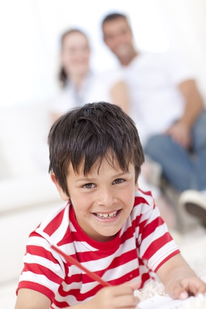 Smiling kid painting on floor in living-room photo