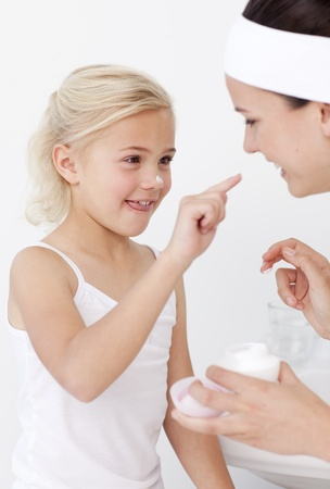 Mother and daughter putting cream on face photo