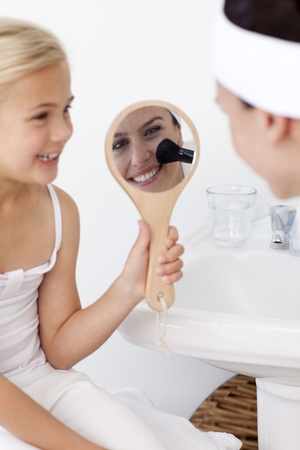 Smiling daughter holding a mirror and mother putting makeup photo