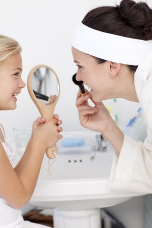 Daughter holding a mirror and mother putting makeup photo