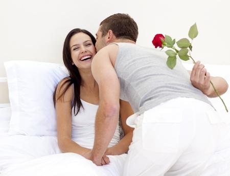 zoenen: Een roos en een kus geven aan zijn mooie vrouw man Stockfoto