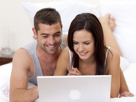 use computer: Couple in bed using a laptop