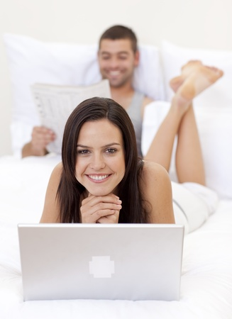 Beautiful woman using a laptop and man reading a newspaper photo
