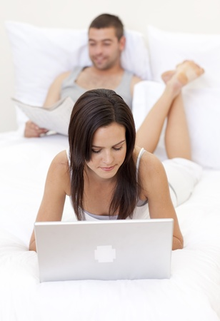 Wife using a laptop and husband reading a newspaper photo