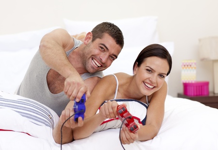 Husband and wife playing videogames in bed photo