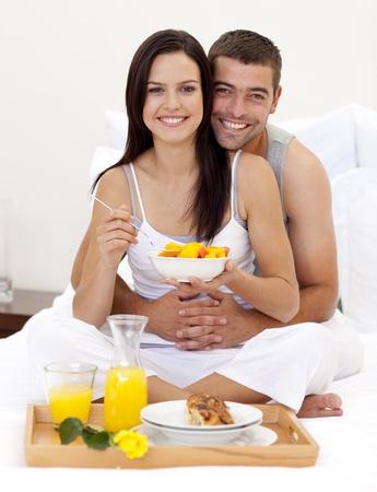 enamorados en la cama: Pareja con desayuno nutritivo en la cama