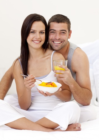 roomservice: Couple eating fruit and orange juice in bed