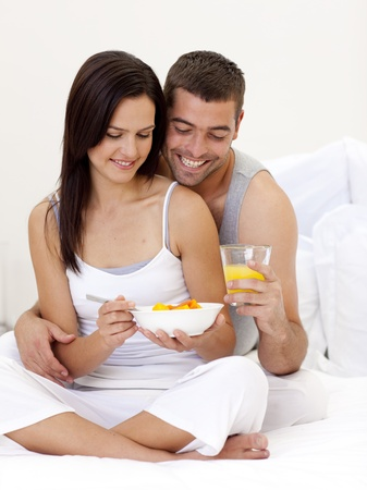 Couple having nutritive breakfast sitting in bed photo