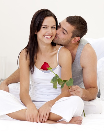 Man kissing a woman and holding a rose photo