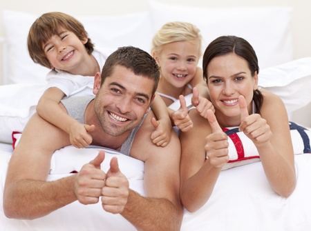 Family playing in bed with thumbs up photo