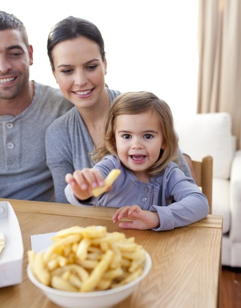 Little girl eating fries at home photo