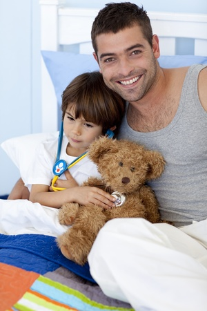 Father and sick son playing doctors in bed photo