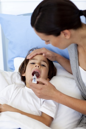 Close-up of mother taking her sons temperature with a thermometer photo