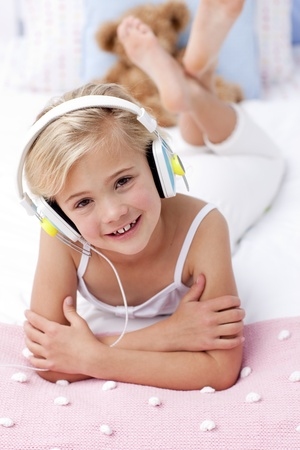 Portrait of little girl lying in bed listening to the music photo